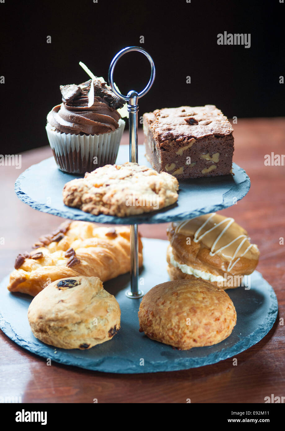 selection of cakes on cake stand - Stock Image