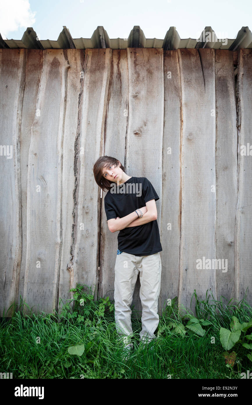 oblique standing teenage boy in front of a wooden wall - Stock Image