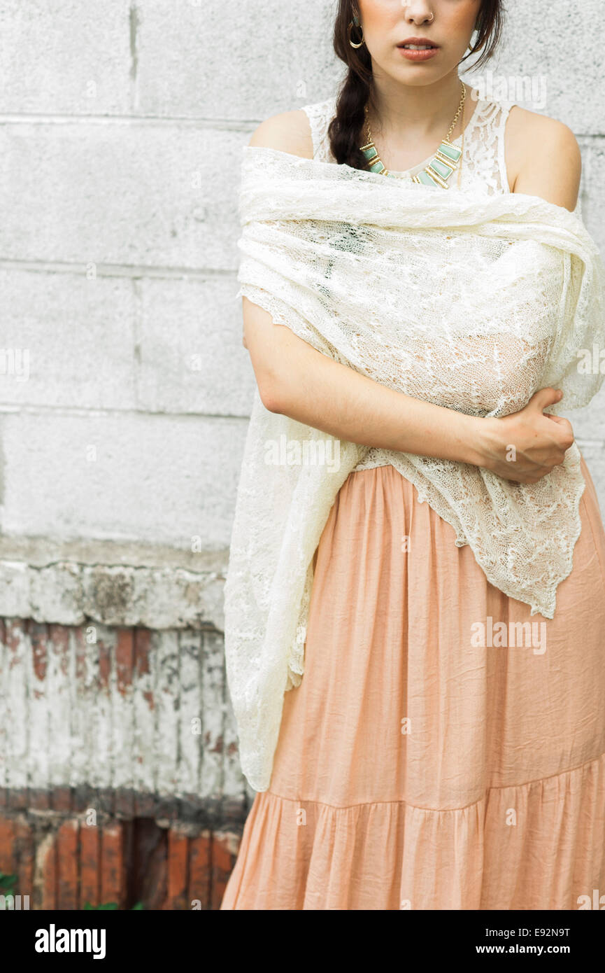 Young Woman with Crocheted Shawl Against Brick Background, Close-Up - Stock Image