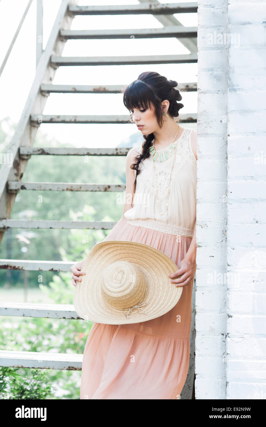 Young Woman in Pink Skirt Holding Straw Hat Next to Fire Escape Stairs - Stock Image