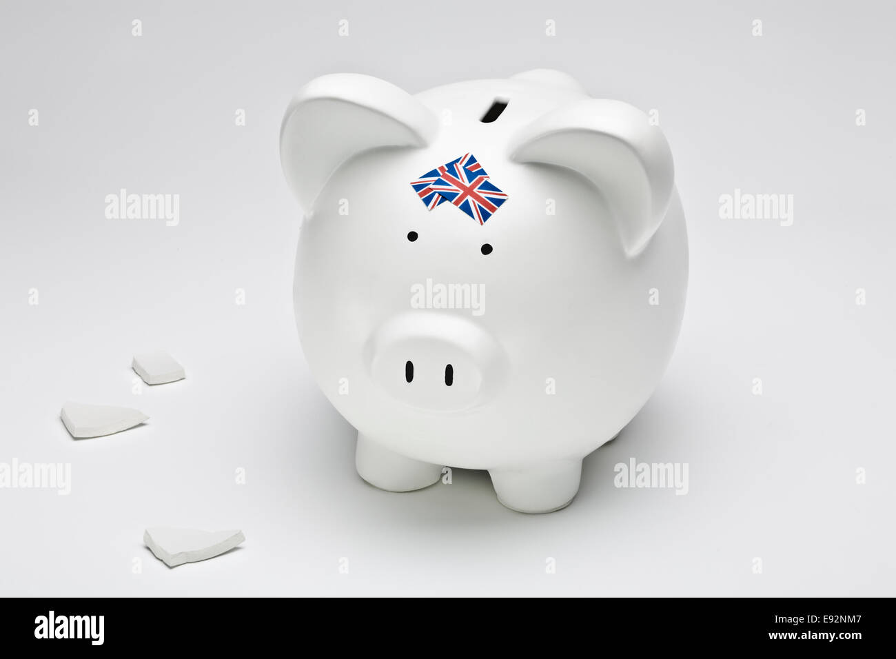 Broken white ceramic piggy bank with UK flags on a white surface - Stock Image