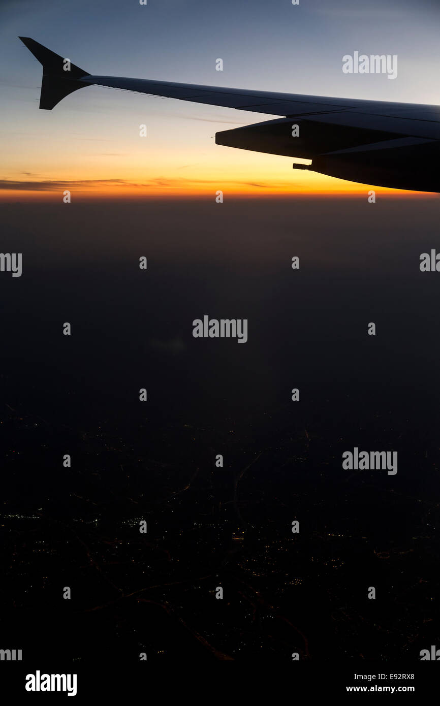 Aeroplane wing against sunrise and land in shadow, flight to Kuala Lumpur, Malaysian Airlines - Stock Image