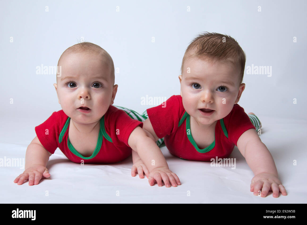 Fraternal 9 month twins boys holding their head ups and looking suspicious or discontented or unsure - Stock Image