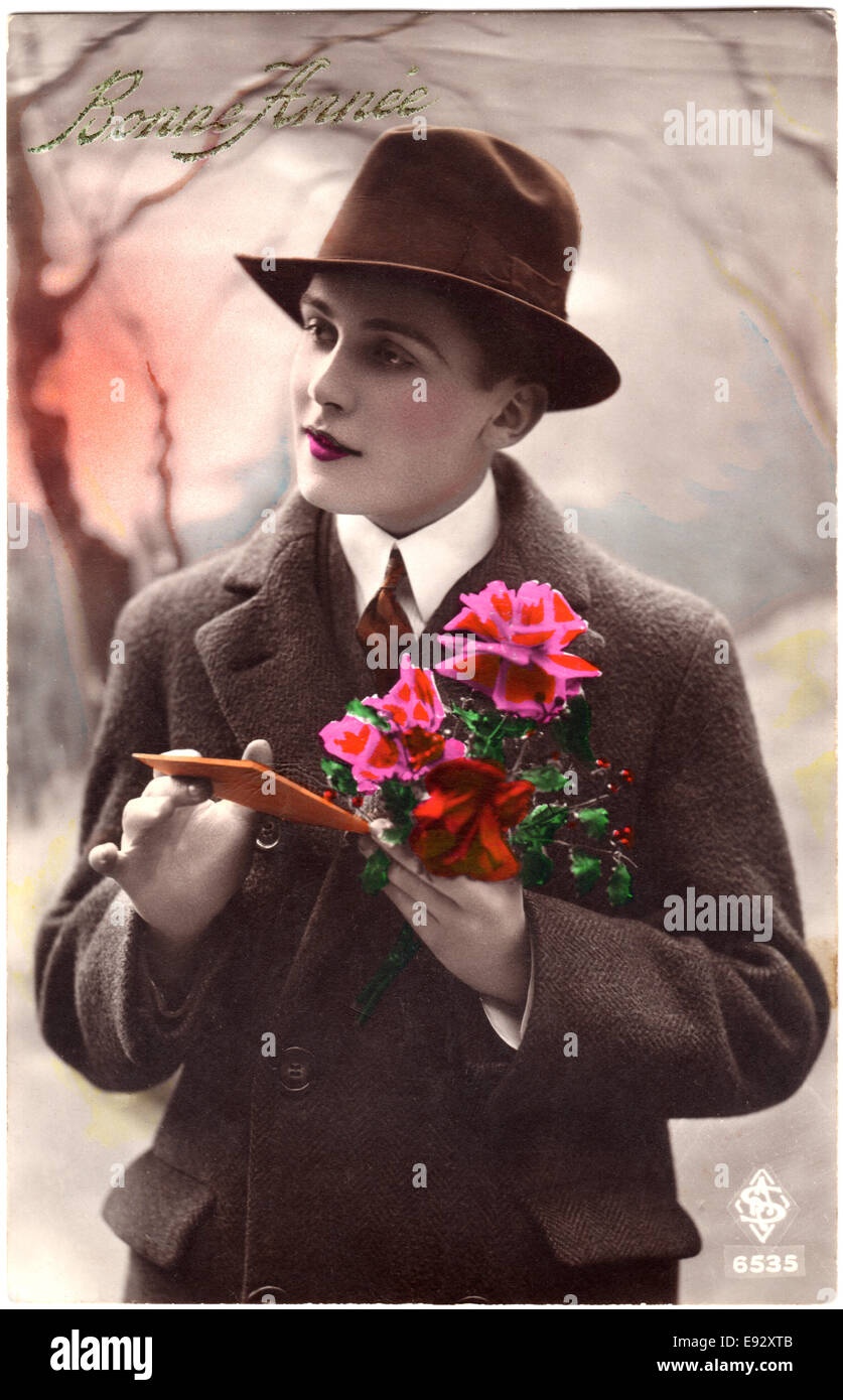 Woman Dressed in Man' Coat and Hat Holding Flowers and Card, 'Bonne France', Hand-Colored French Postcard, - Stock Image