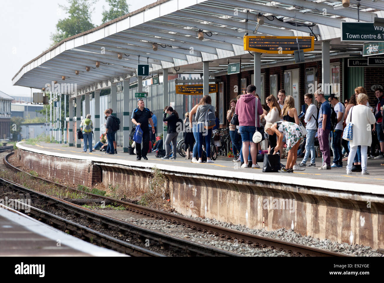 Passengers waiting on the platform of Chichester station, West Sussex - Stock Image