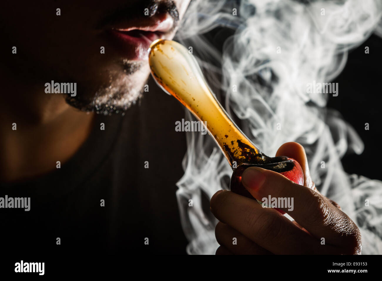 studio shoot with model simulating smoking pot with a pipe in a dark high contrast image - Stock Image