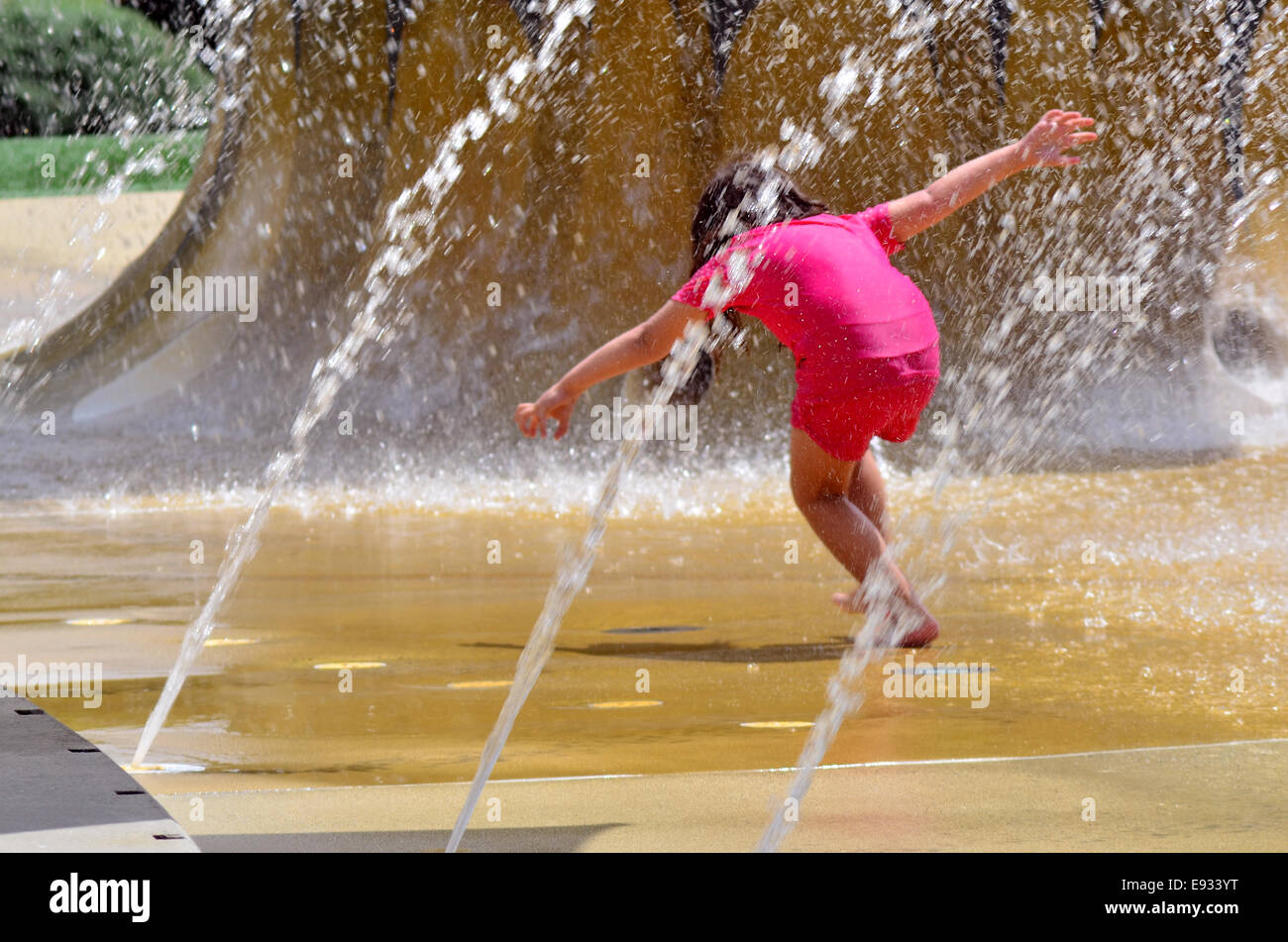 Child (girl age 04) play with water fountain. concept photo hot weather and heatwave. copyspace - Stock Image