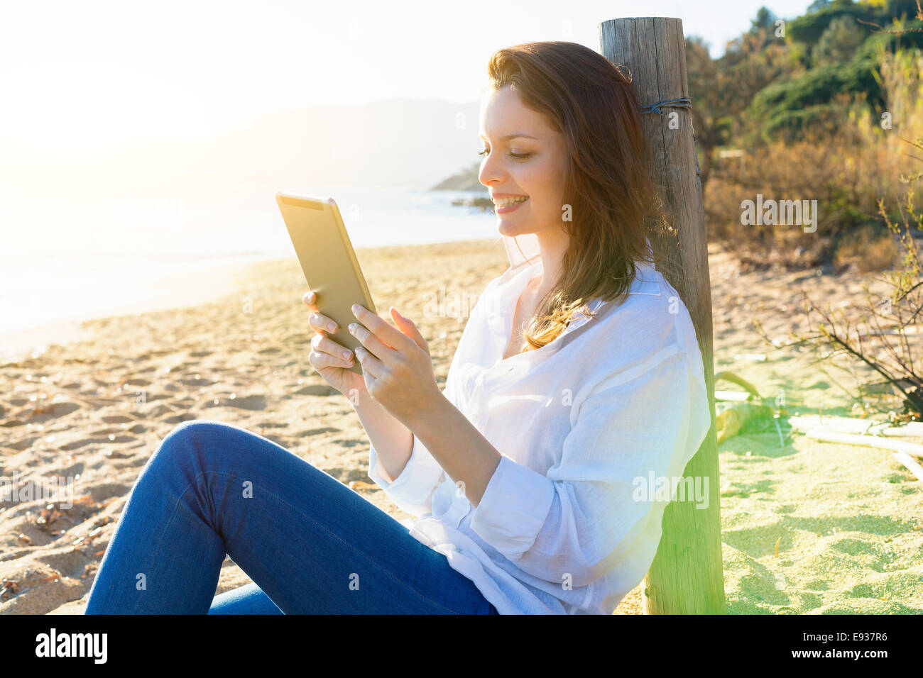 Woman Using a Digital Tablet on the beach - Stock Image