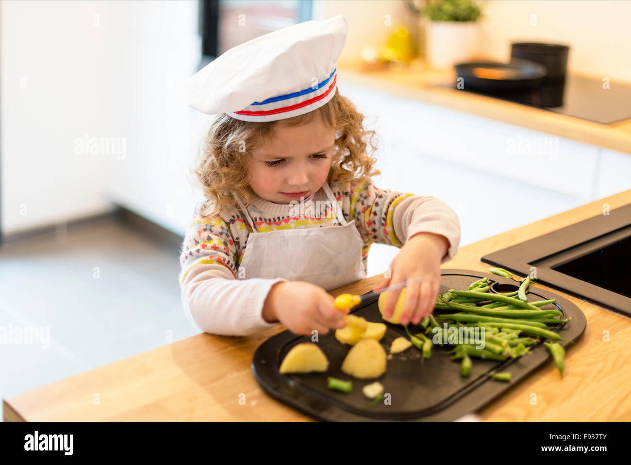 Portrait of little chef cooking - Stock Image
