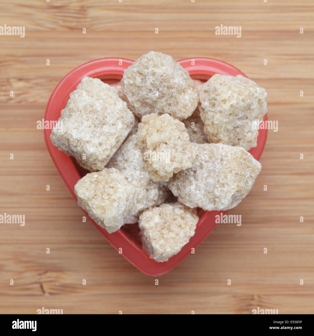 Brown cane sugars in a heart bowl. Close-up. - Stock Image