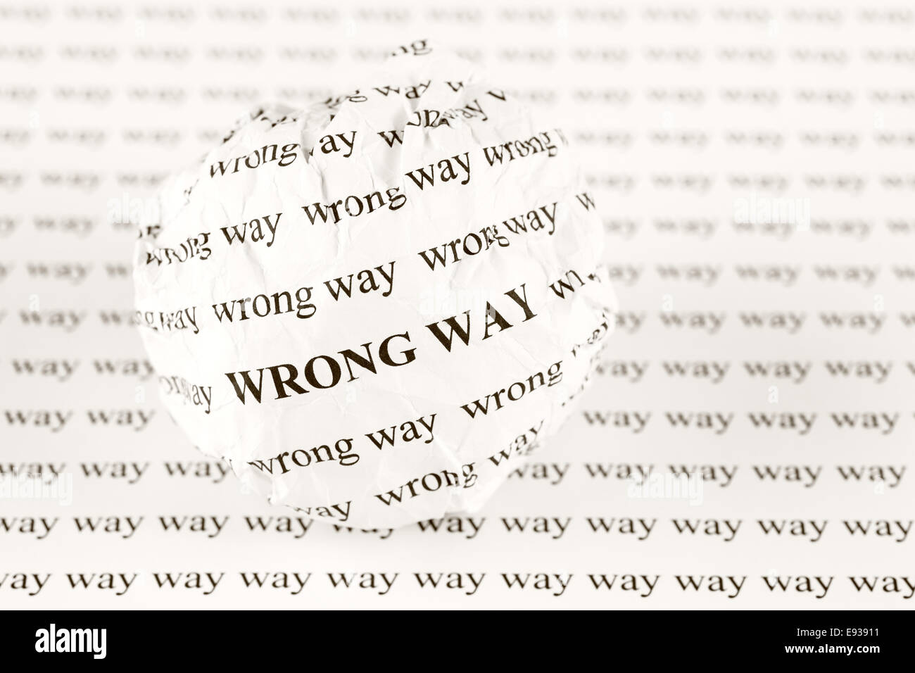 Crumpled paper ball with words 'wrong way' on background with words 'way'. Sepia. - Stock Image