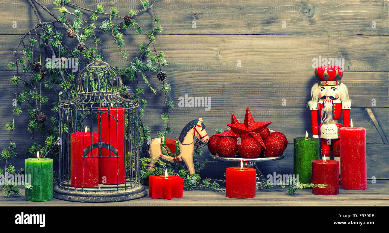 christmas decorations with red candles antique toys nutcracker and rocking horse vintage style toned picture