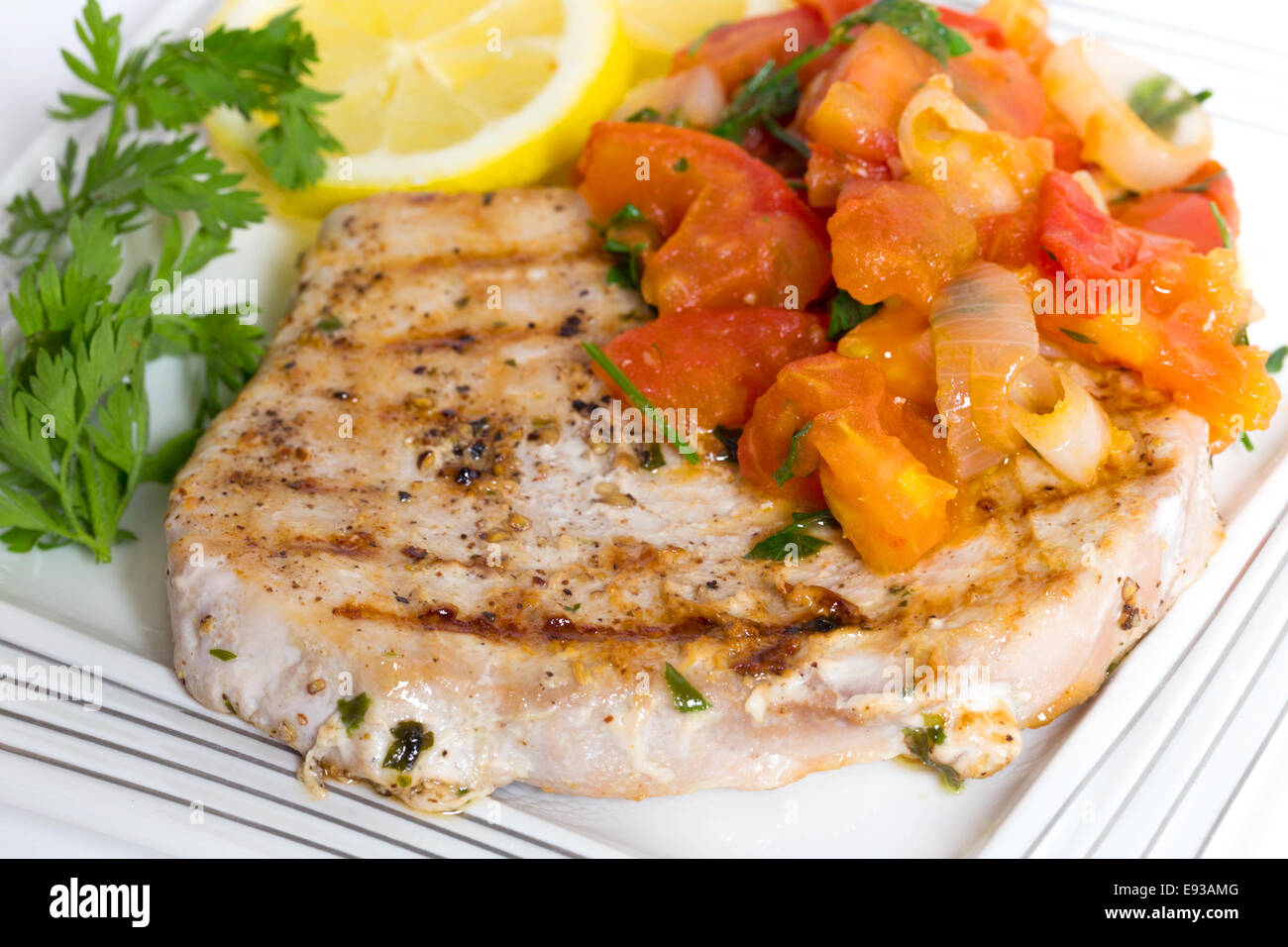 Grilled marlin steak served with an onion, garlic and tomato salsa, sliced lemon and parsley - Stock Image