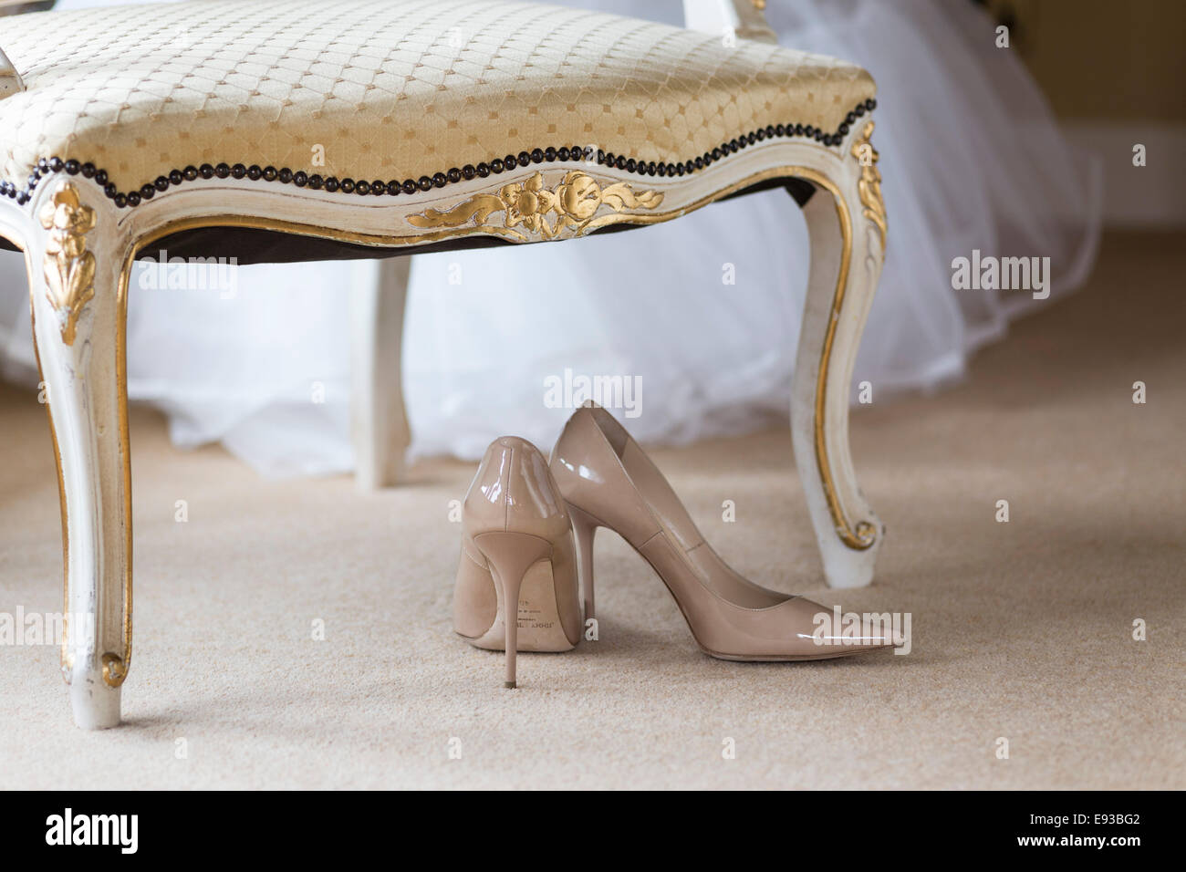Wedding shoes beneath chair Stock Photo