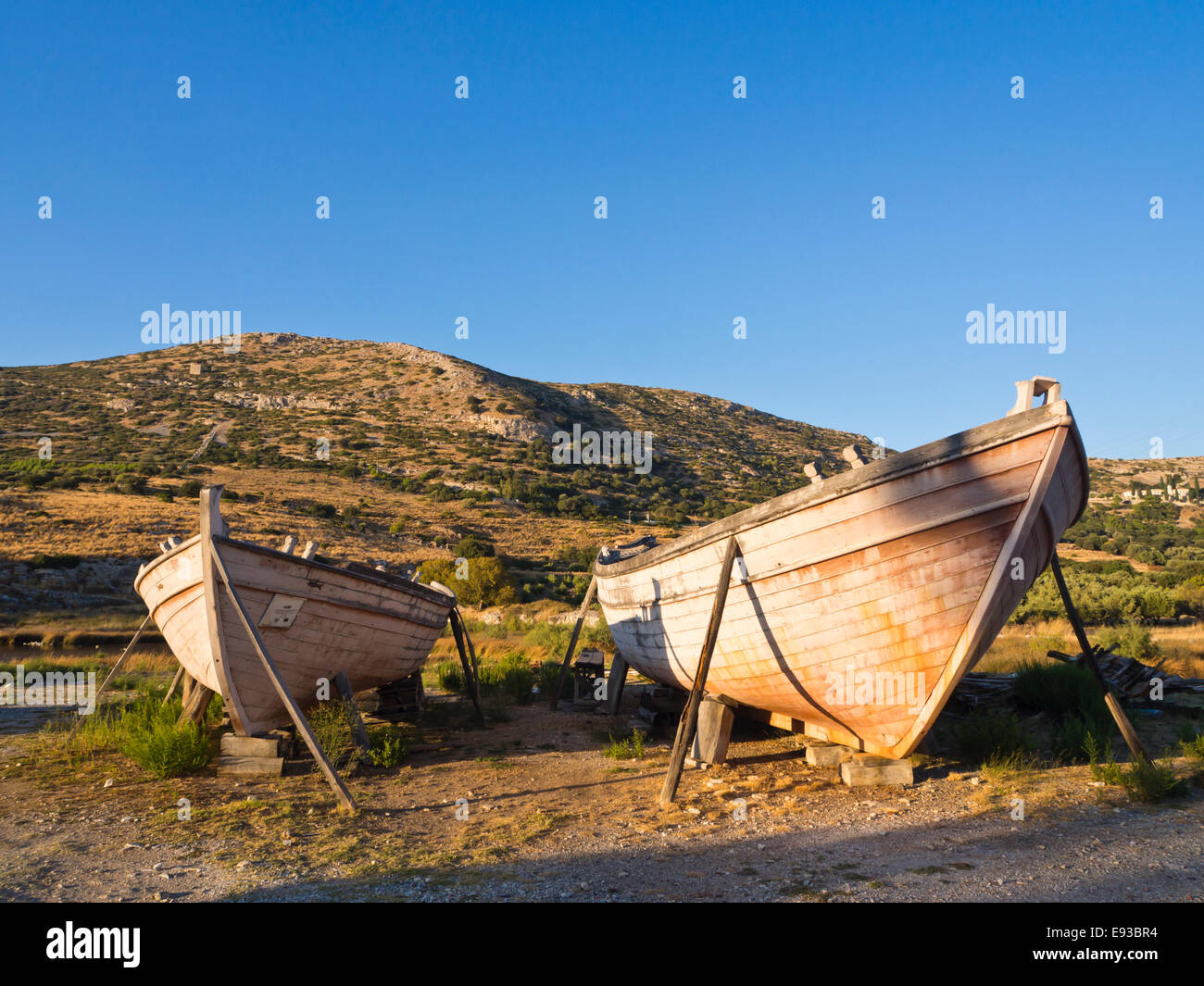 Greek wooden fishing boat hulls placed as roadside decoration, golden evening light colouring the countryside, Samos Stock Photo