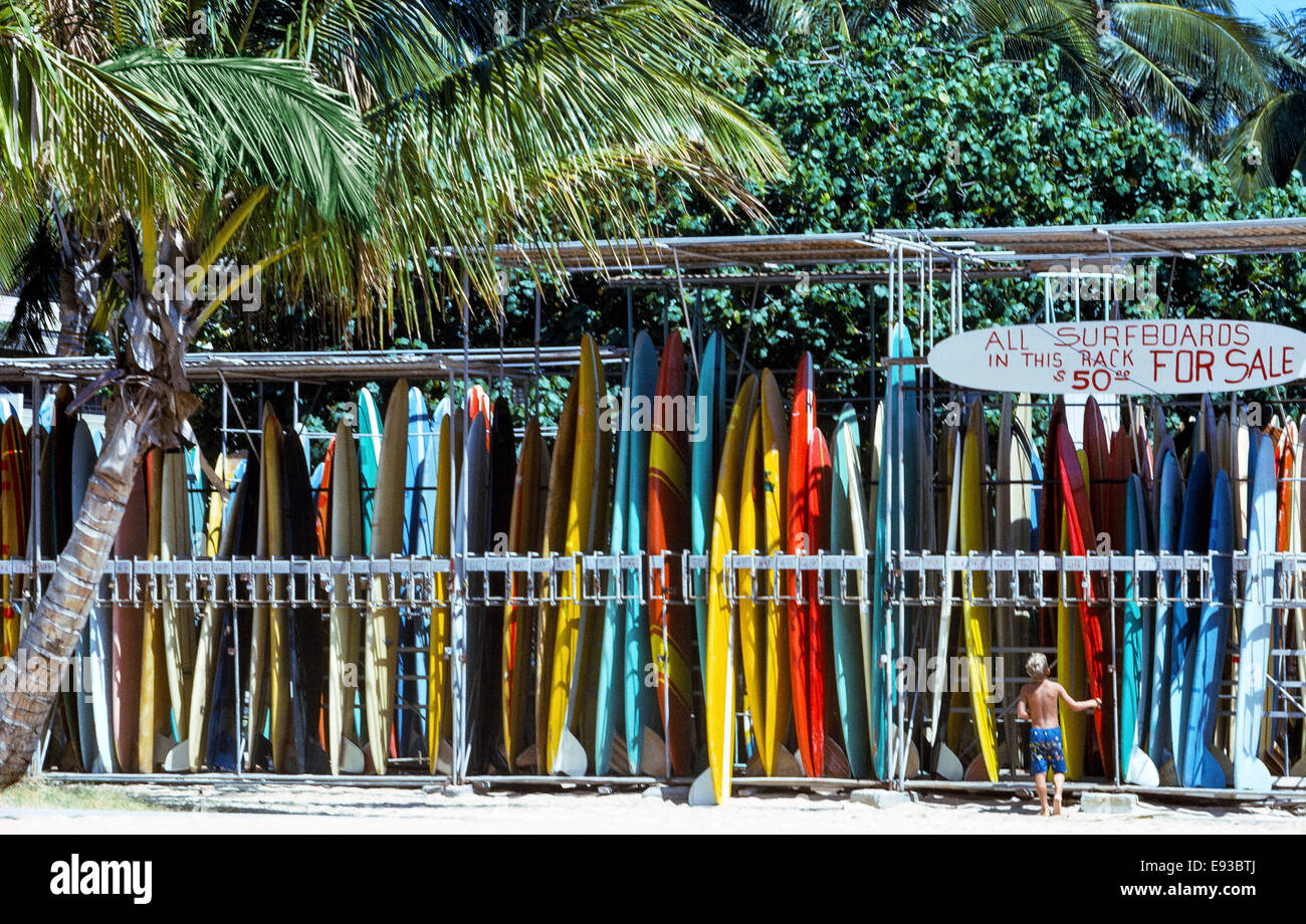A very young surfer looks at the classic 1960s Hawaiian surfboards that are for sale and for rent on Waikiki Beach - Stock Image