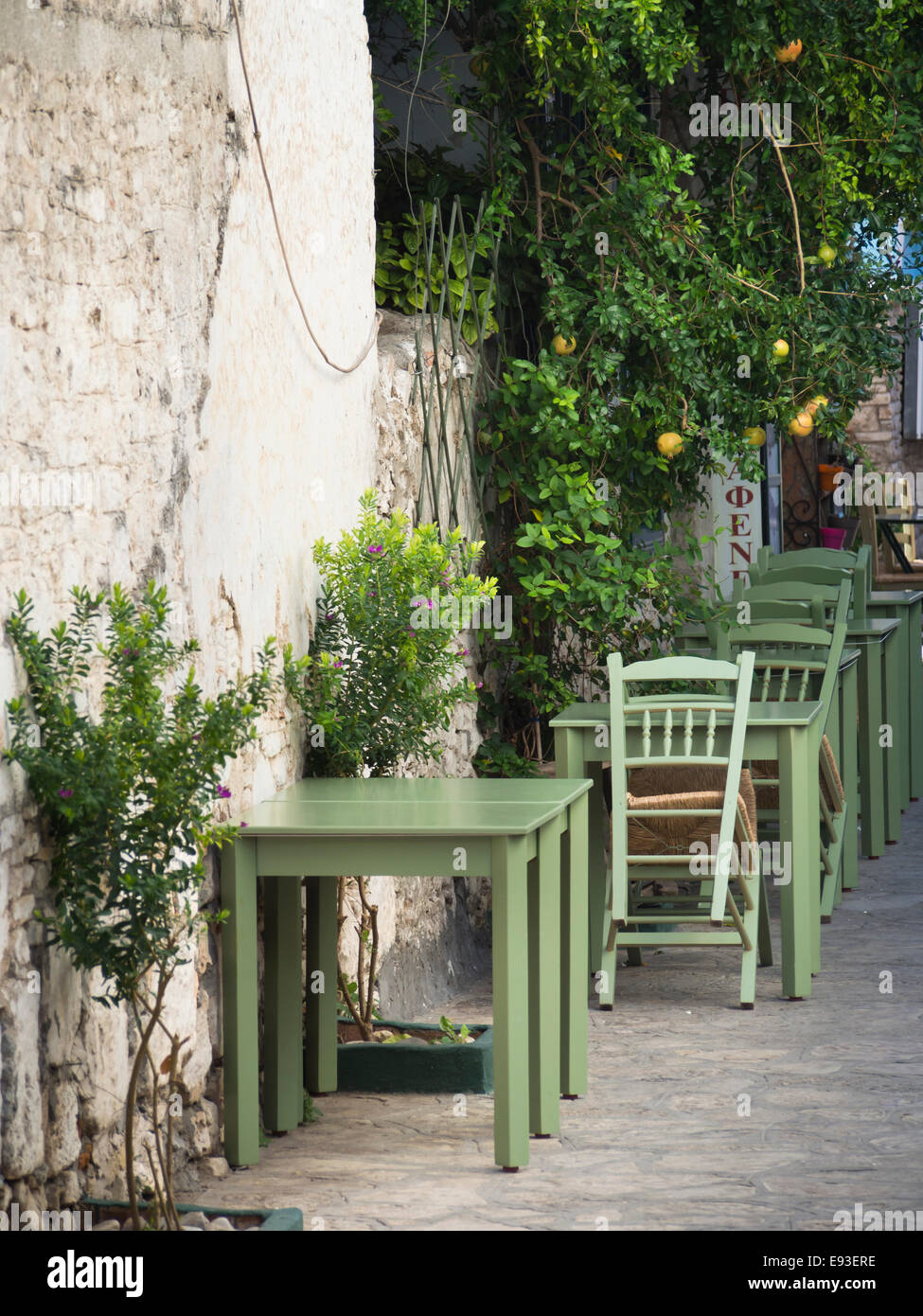 Typical Greek pavement café, colourful green wooden tables and chairs, Pythagoreion village in the island of Samos Stock Photo