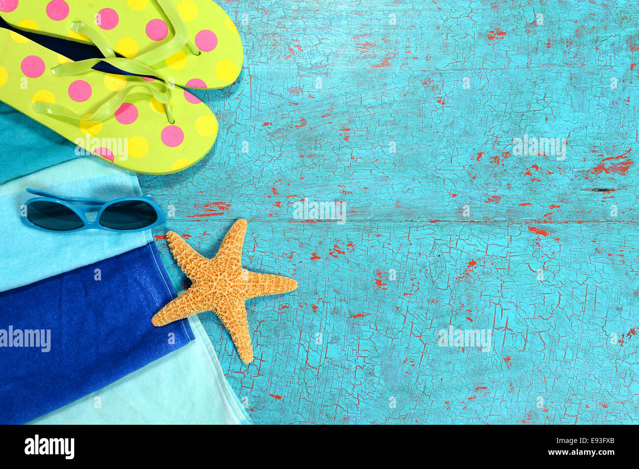Beach towel, sunglasses, starfish and flip flops over painted wood planks - Stock Image