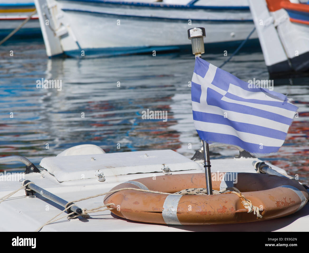 Faded Greek flag on a fishing boat in the harbour of Pythagorion in Samos island Greece. Stock Photo