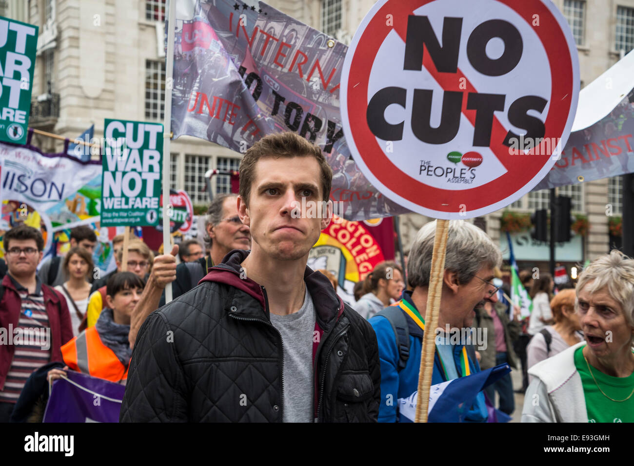 Angry looking young man with No Cuts placard. Britain Needs a Pay Rise march, London, 18 October 2014, UK Credit: - Stock Image