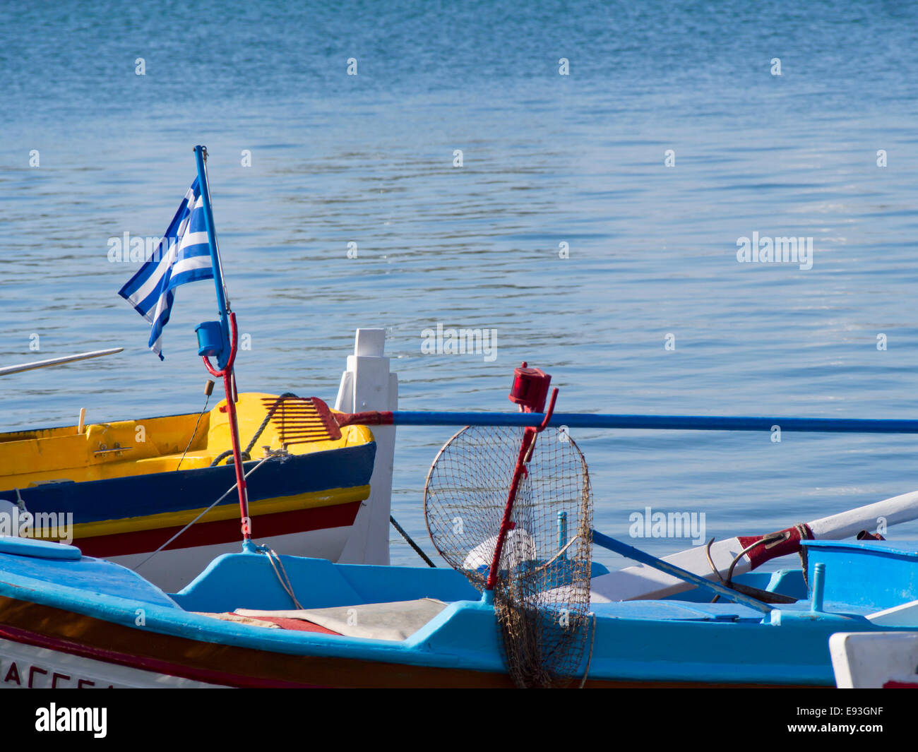 Fishing boat in the harbour of Pythagorion in Samos island Greece. Blue colours of sea, Greek flag and boat, holiday Stock Photo