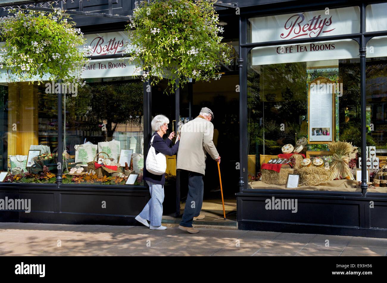 Senior couple entering Betty's tearoom in Ilkley, North Yorkshire, England UK - Stock Image