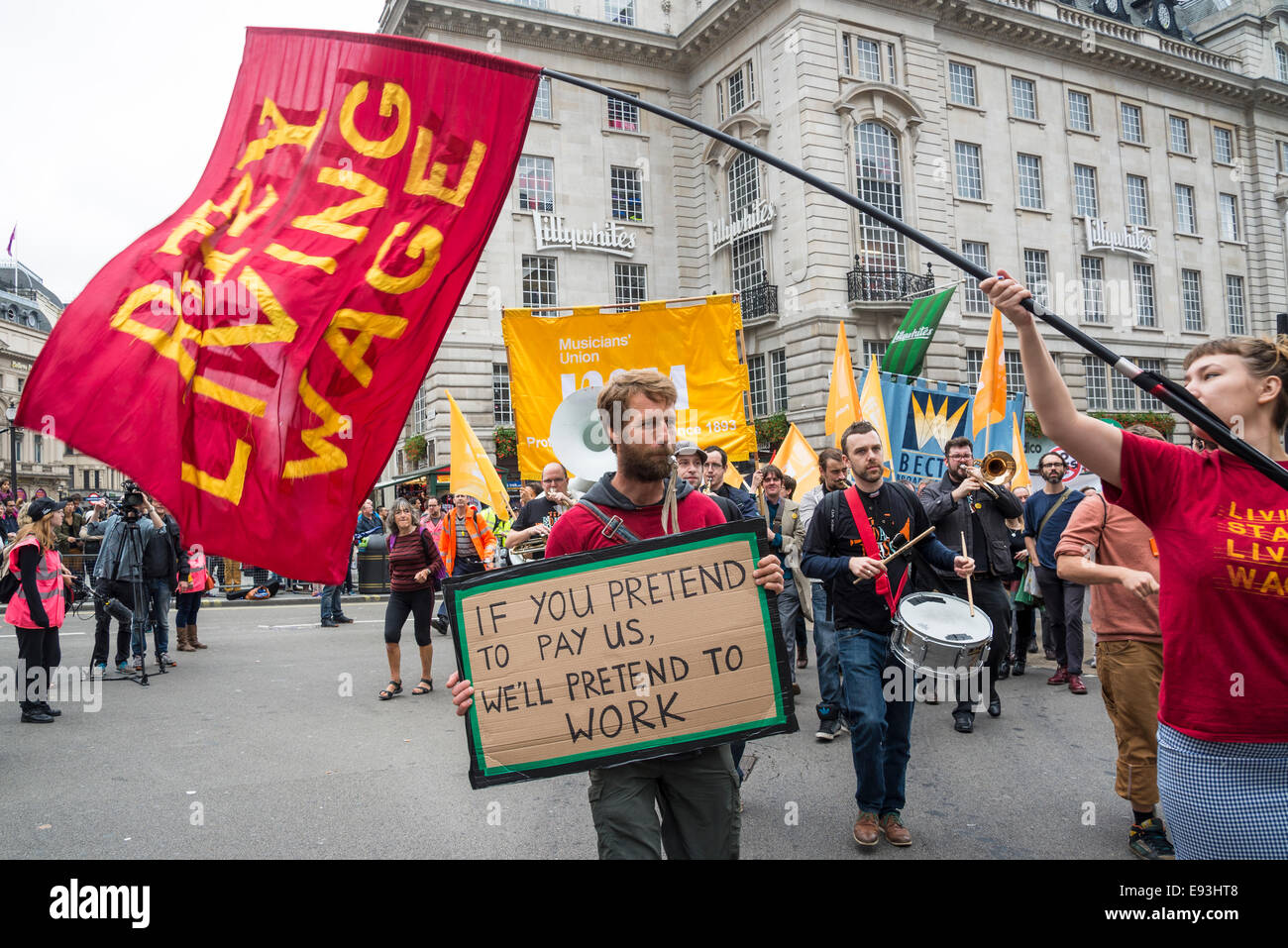 Man carrying hand-made placard 'If you pretend to pay us, we'll pretend to work', 2014. Britain Needs - Stock Image