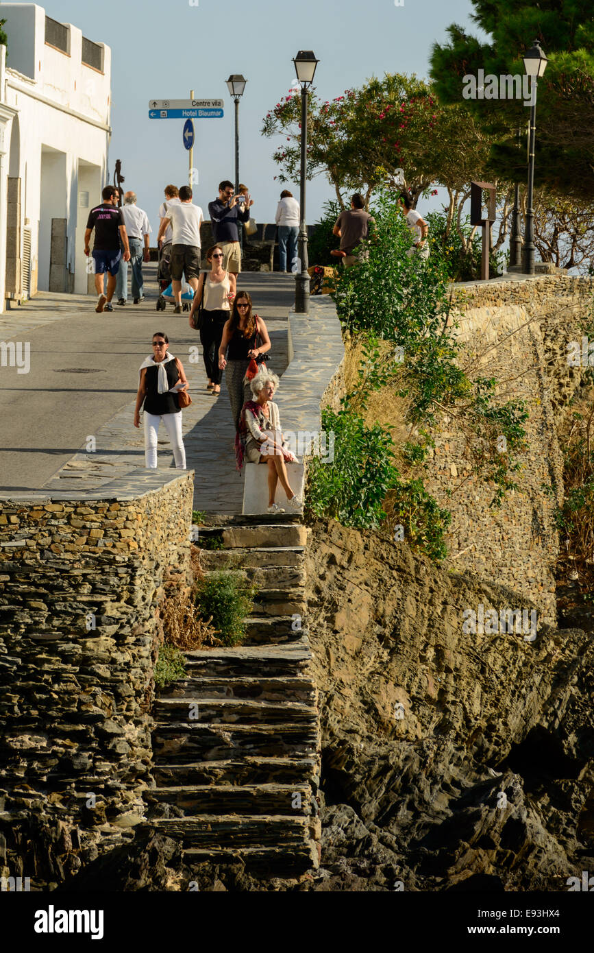 People enjoying a walk along the sea walk during a sunny summer afternoon in the town of Cadaques. - Stock Image