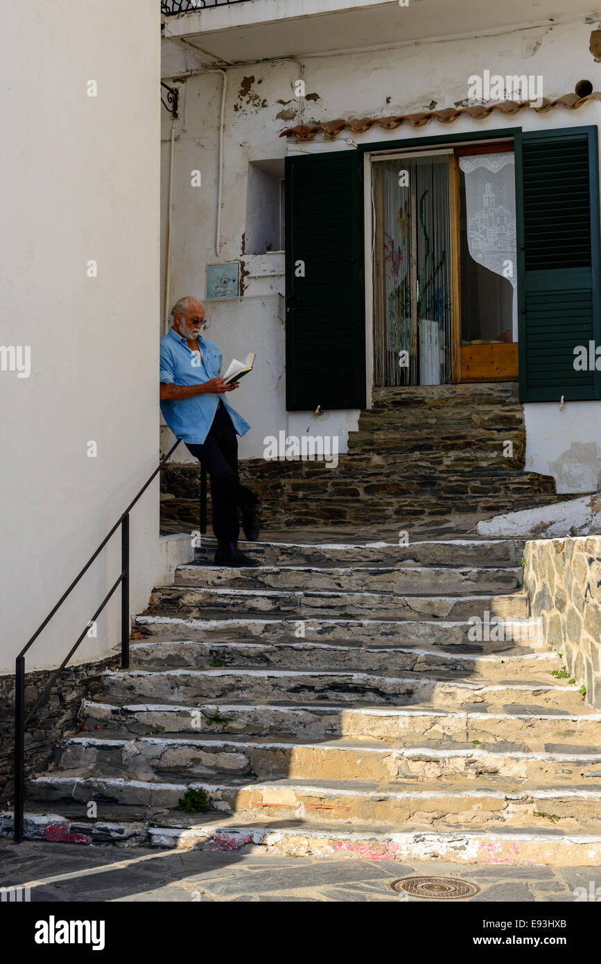 An old man read a book in the shade during a hot summer day. Town of Cadaques, Catalunya. - Stock Image