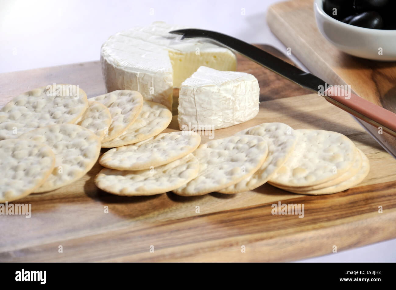 Close of up of cheese platter with Camembert cheese and water crackers on wooden boards and white tablecloth. Stock Photo