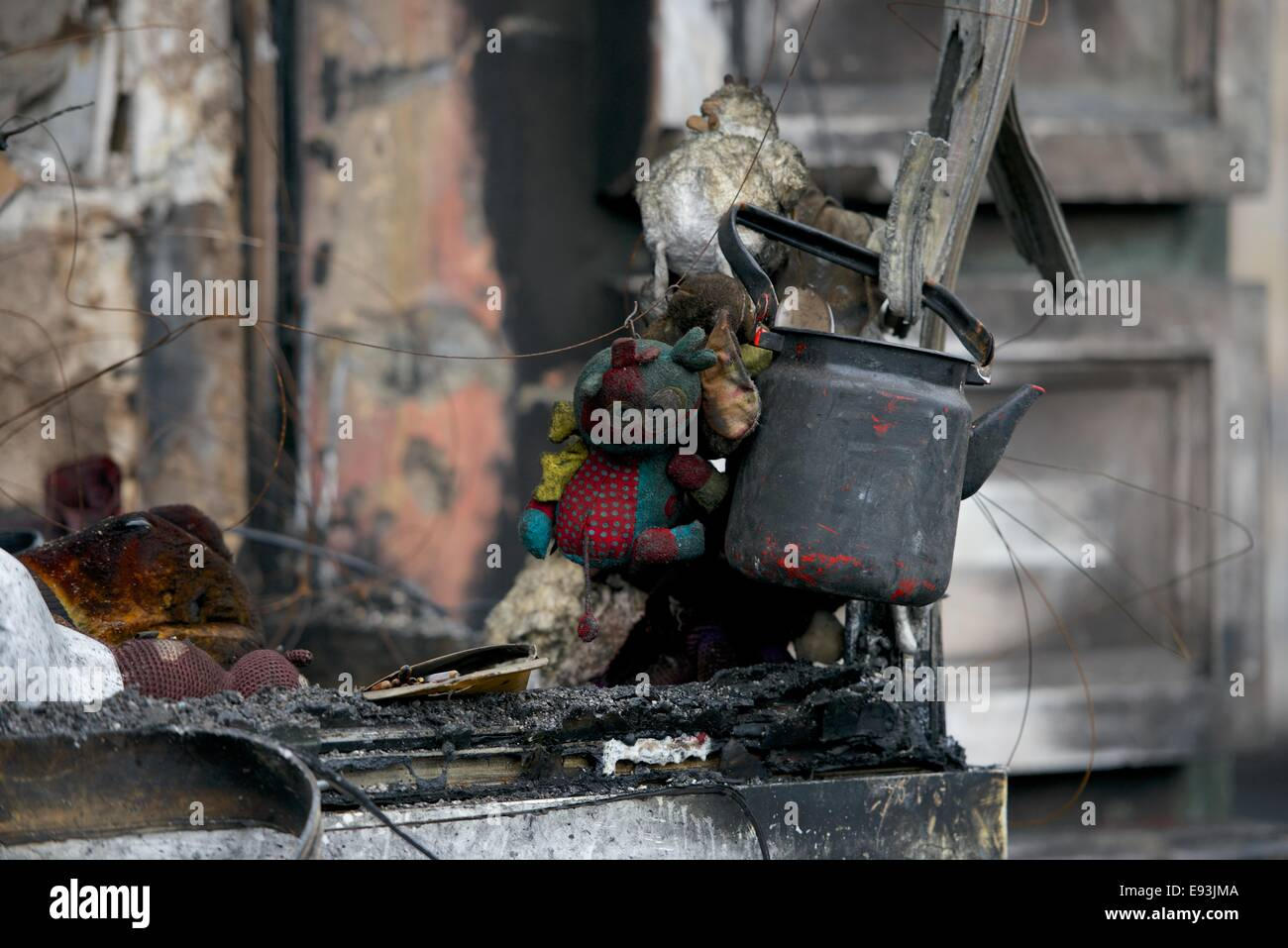 A soot covered teapot and childs knitted toy hang froma burned out shop window in Kiev - Stock Image