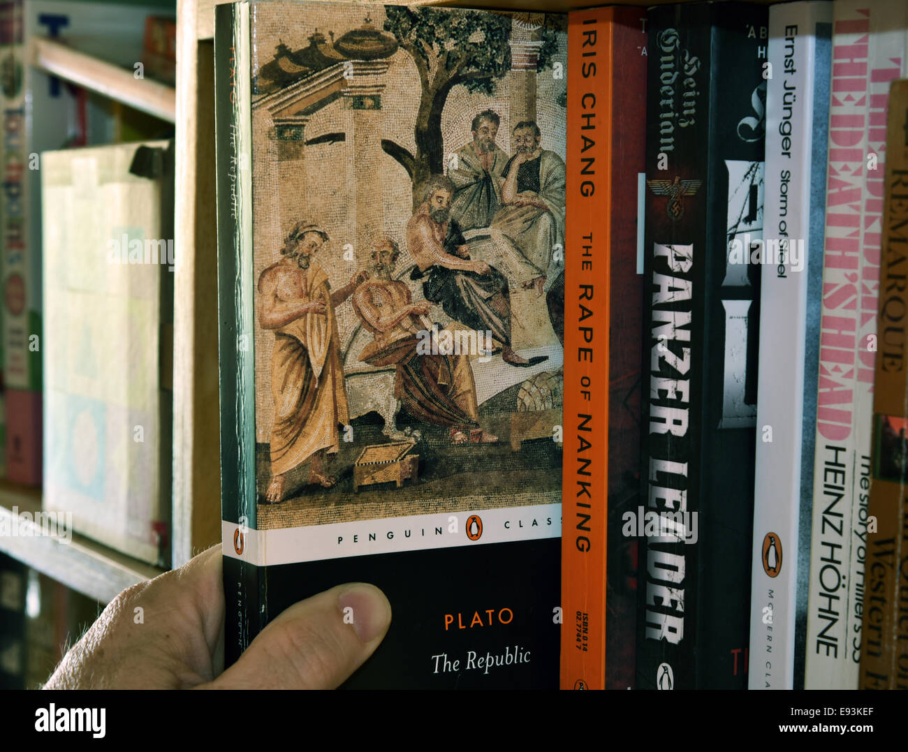 A hand removing a copy of Plato's The Republic from a bookshelf - Stock Image