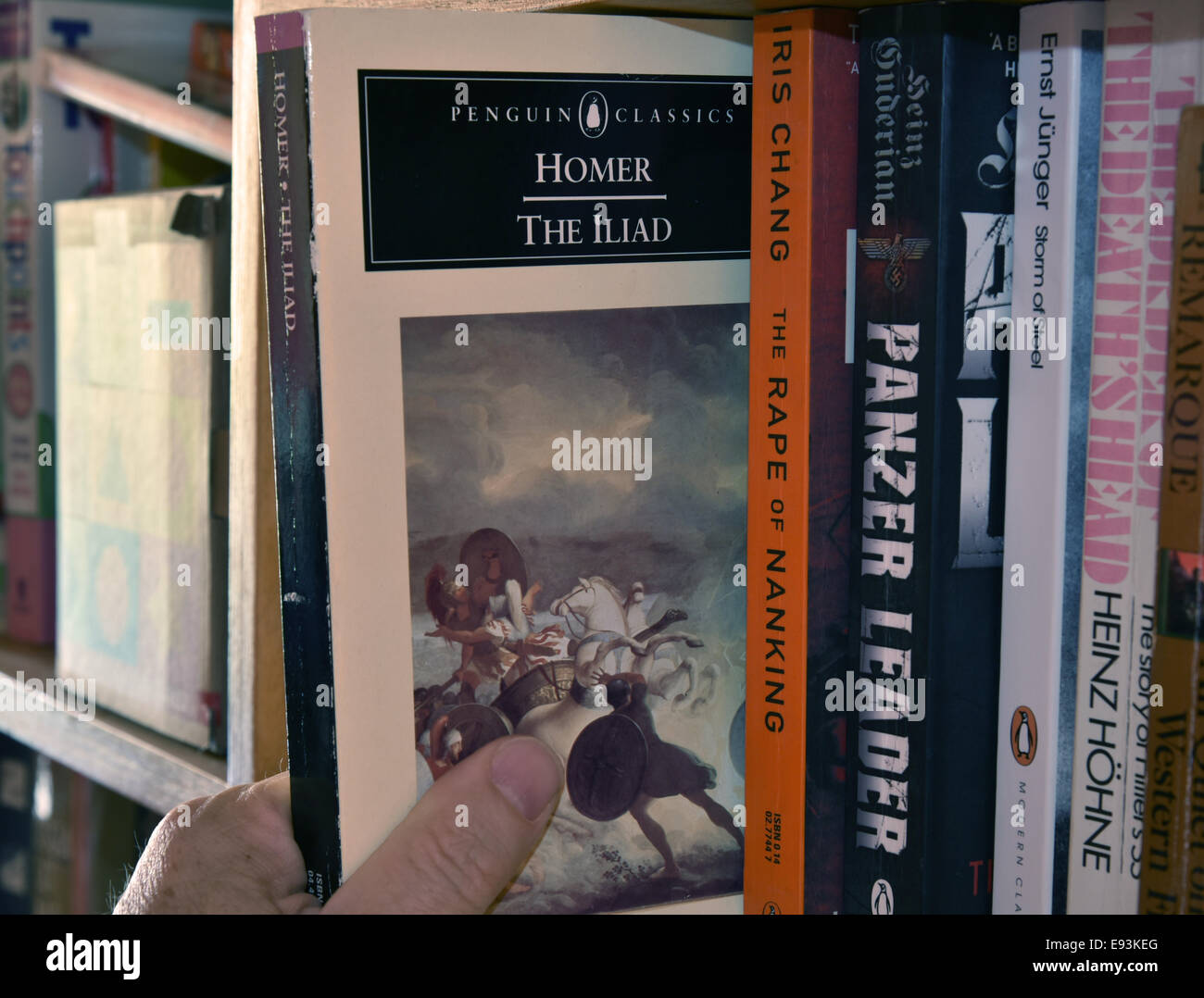 A hand removing a copy of Homer's The Iliad from a bookshelf - Stock Image