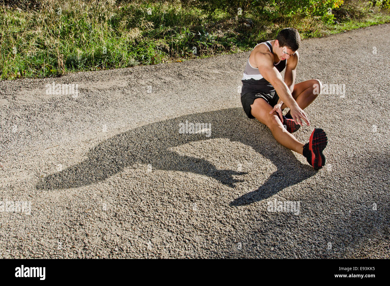 Runner man warming arms with sun light shadow, warm up and stretching - Stock Image