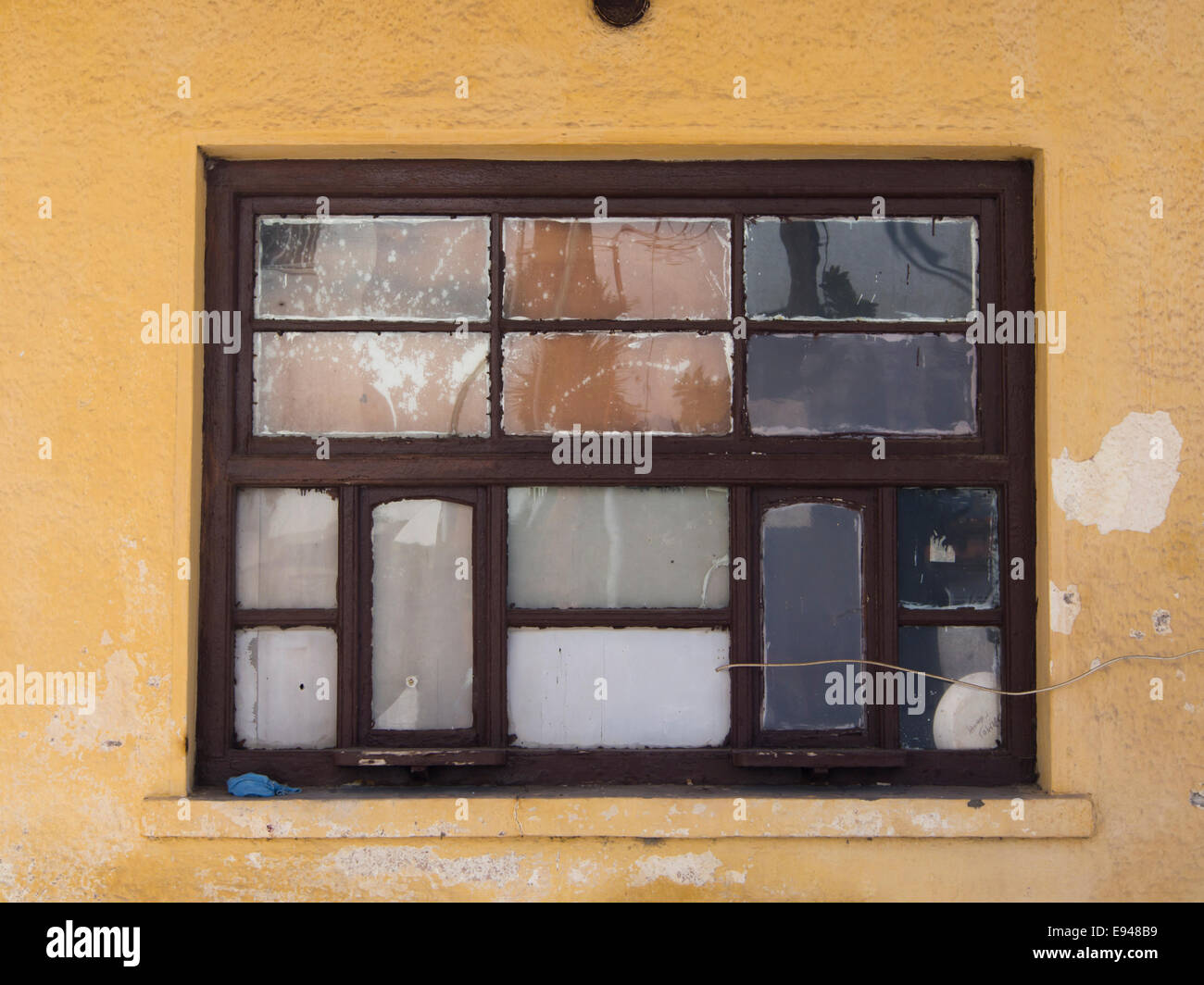 Old weathered window with 14 rectangular window panes subdued colour palette in yellow tan and brown, Samos Greece - Stock Image