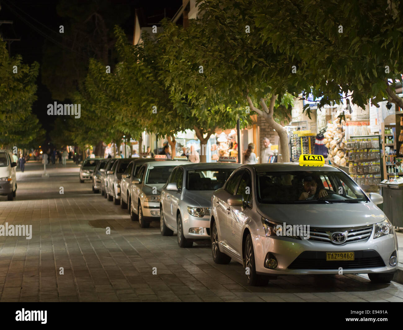 Line of taxis in late evening in the harbour of  Pythagorion on Samos island in Greece transport for tourists income Stock Photo
