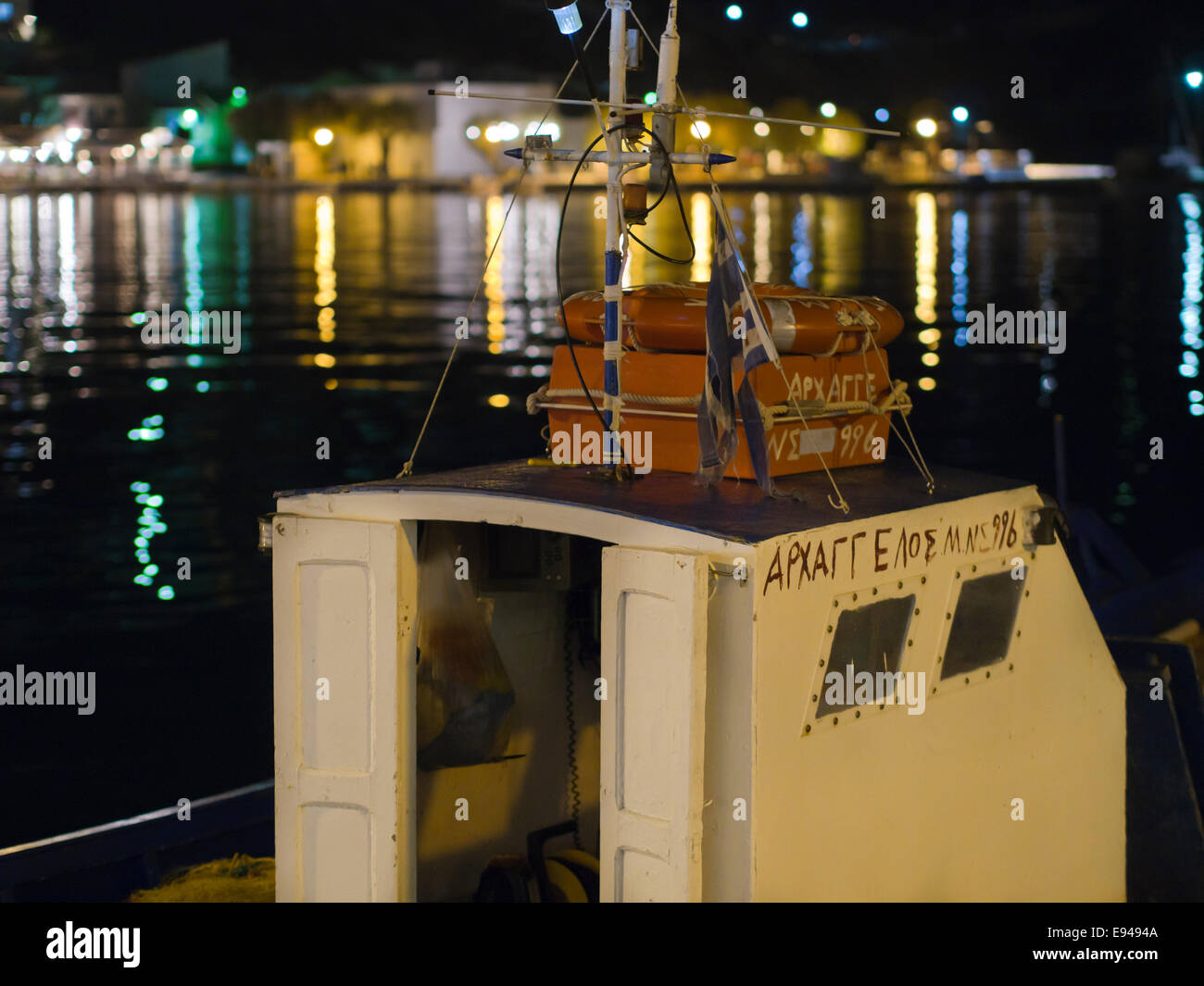 Greek fishing boat and colourful harbour lights, late evening or night in the harbour of  Pythagorion on Samos island Stock Photo