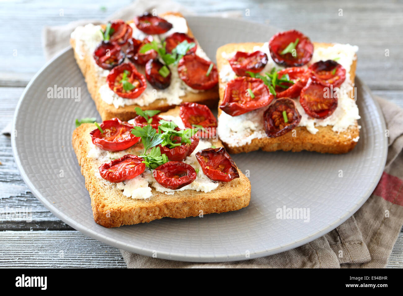 Bruschetta with sun-dried tomatoes and cheese, delicious food - Stock Image