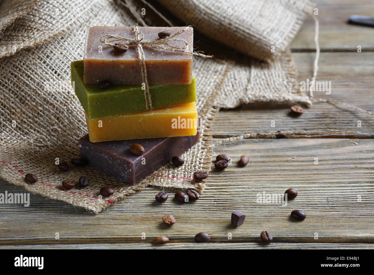 Handmade soap with roasted coffee beans, toiletries on sacking - Stock Image