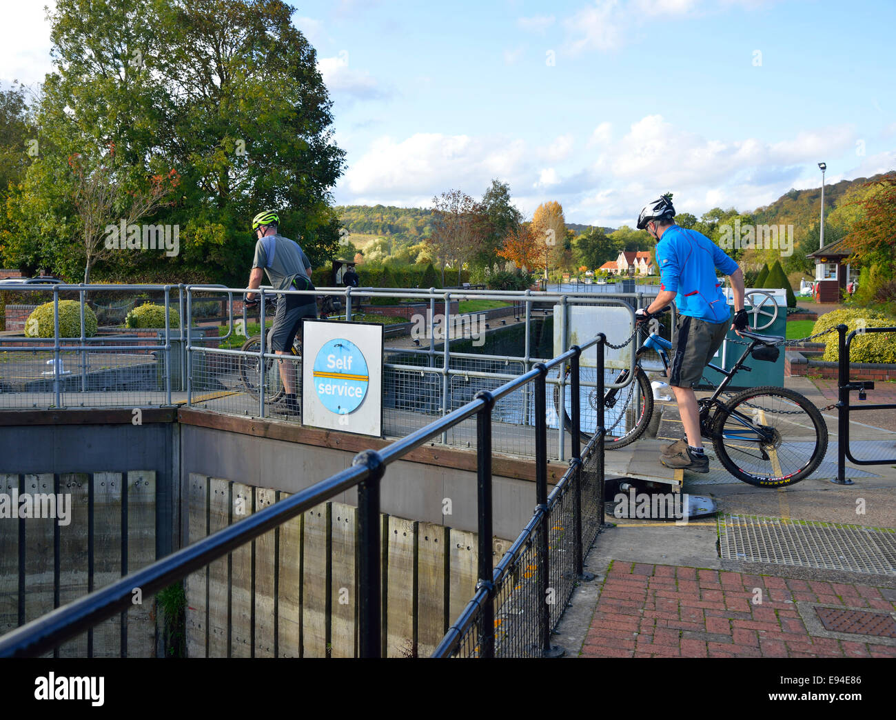 Two cyclists  on mountain bikes crossing Hambleden Lock gates on the River Thames, on the Oxfordshire/Buckinghamshire - Stock Image