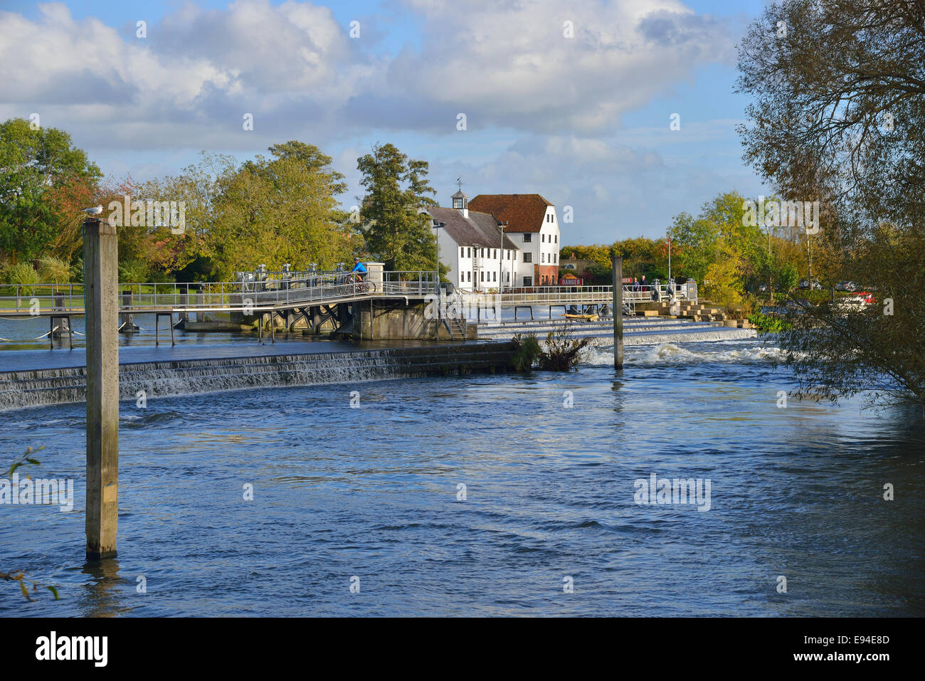 Looking across to the historic Hambleden Mill and weir with footbridge over the River Thames, Mill End,  Hambledon, - Stock Image