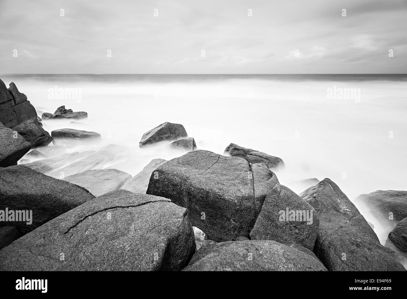 Long exposure with granite boulders at Anse Bazarca in the south of Mahe, Seychelles during a storm - Stock Image
