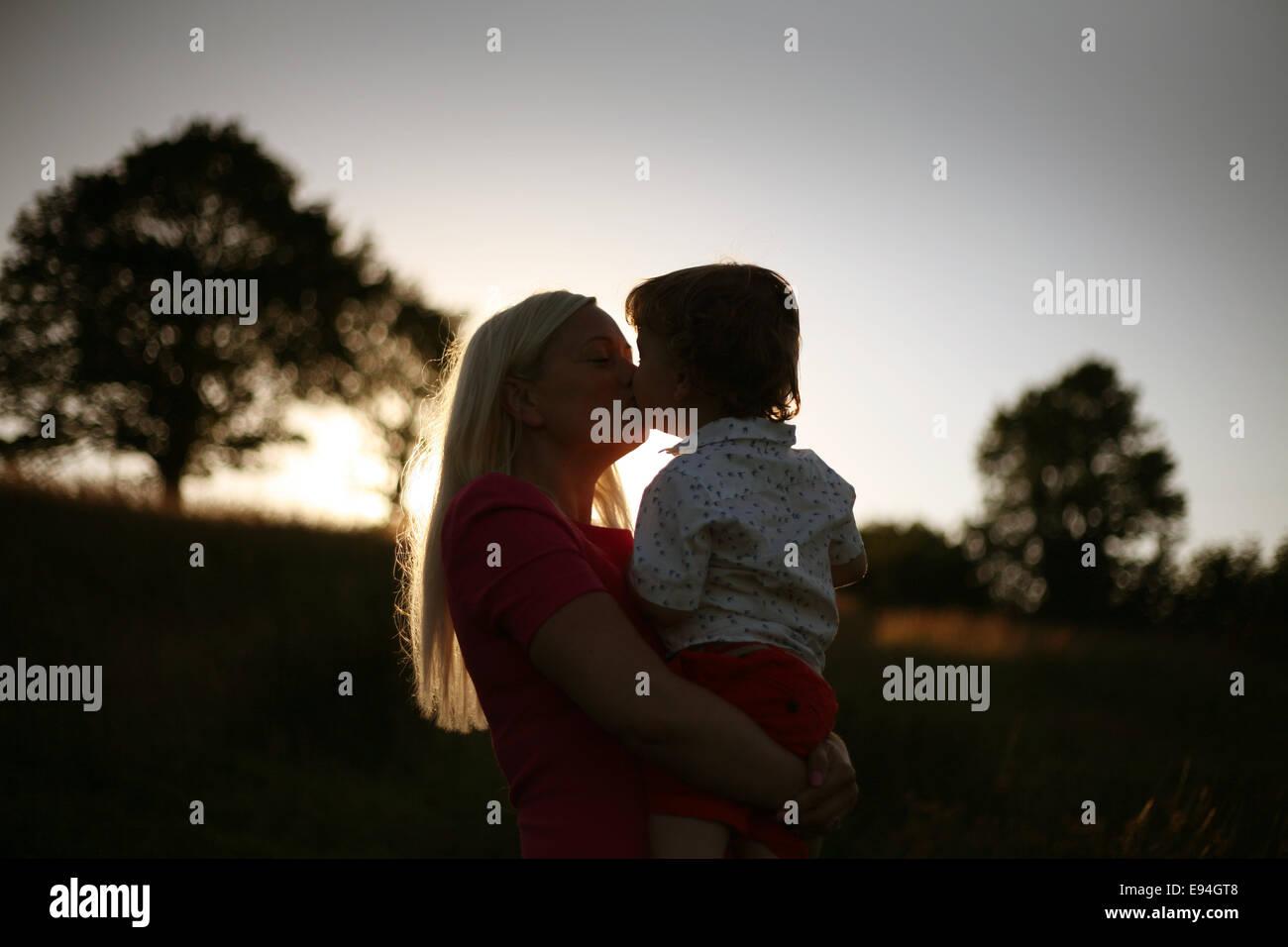 mum holding baby boy at sunset - Stock Image