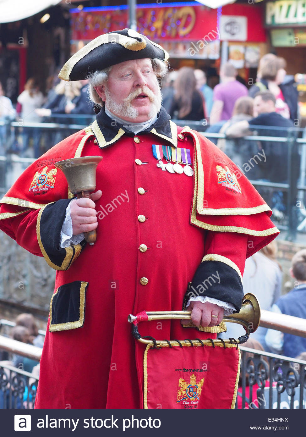 View of a traditional town crier  with bright red coat and holding a handbell and  bugle - Stock Image