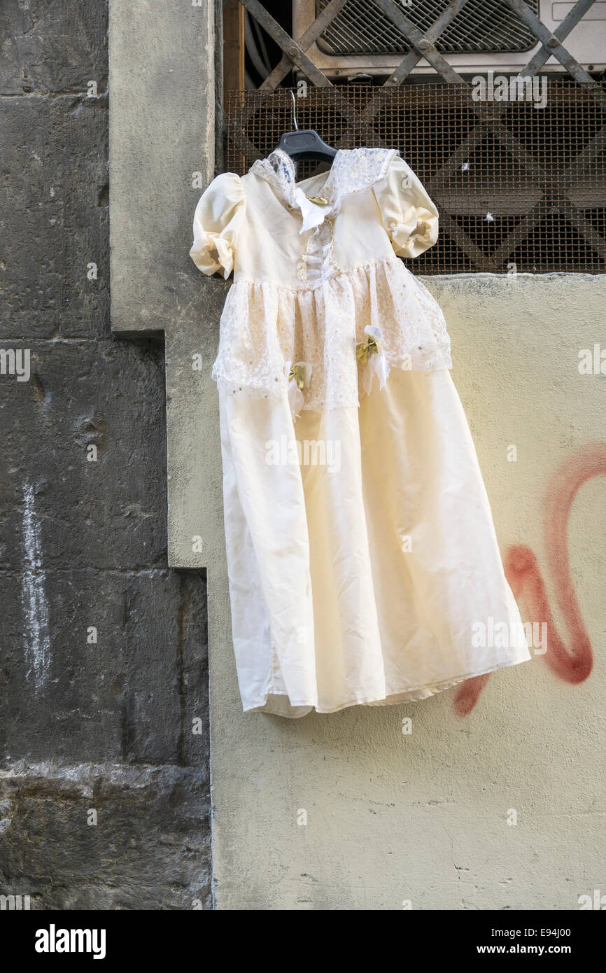 exquisite little girl's christening gown trimmed with lace displayed hanging on a window grate outside 2nd hand - Stock Image