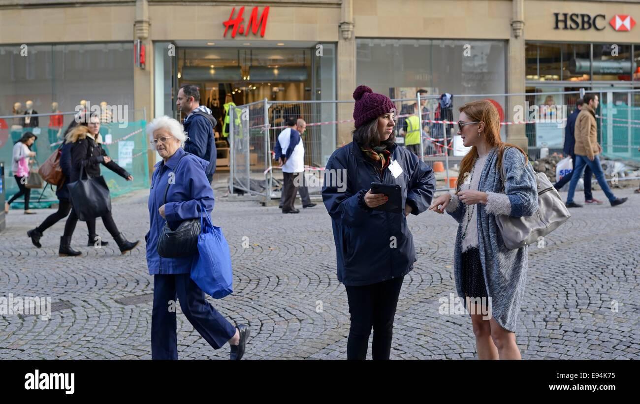 Woman talking to shoppers in street survey in pedestrian precinct - Stock Image