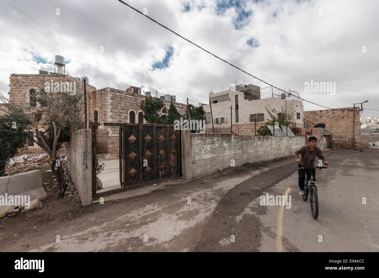 Hebron, Israel/West Bank. An Arab boy rides his bicycle in the street near stone houses. - Stock Image