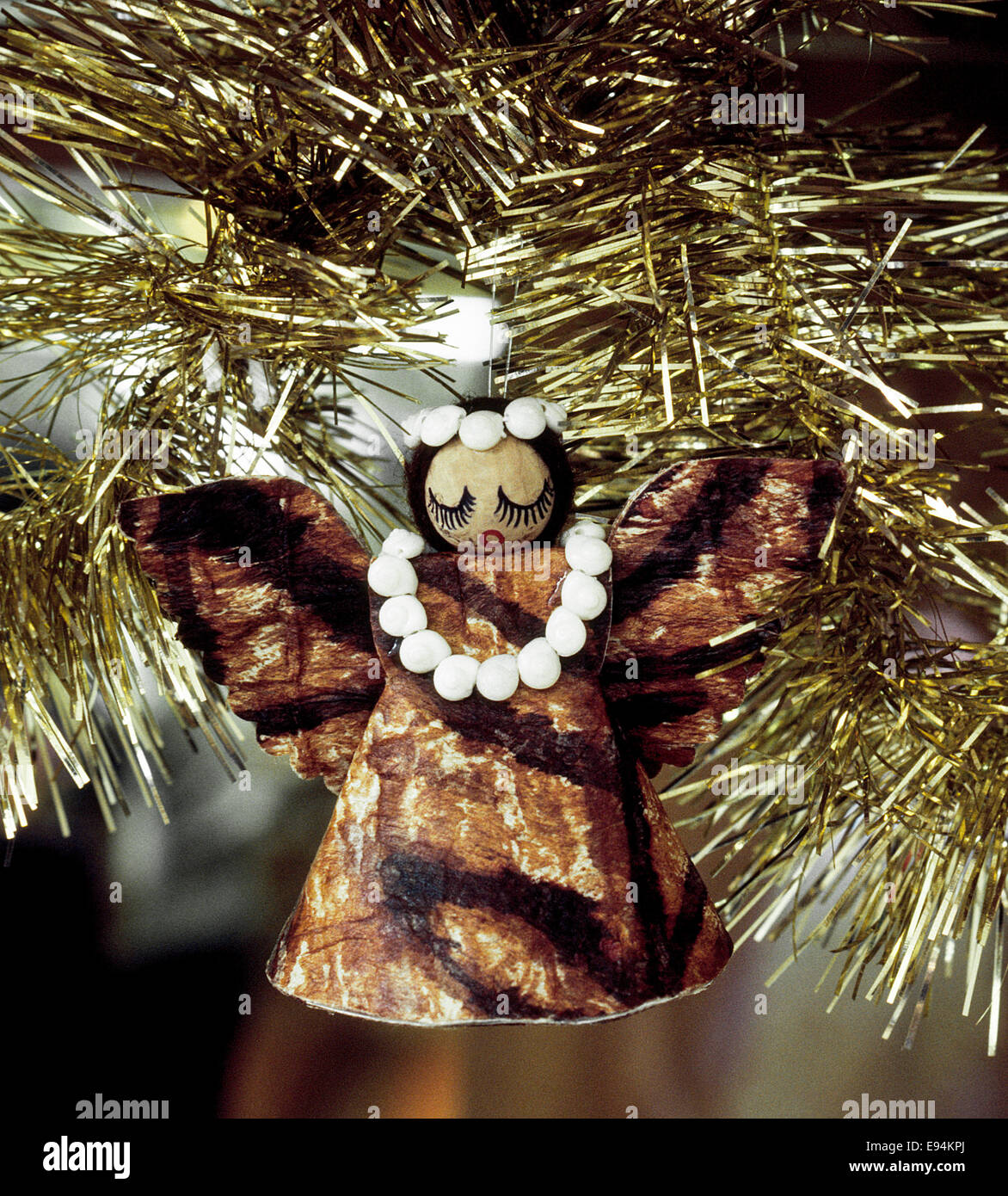 A Hawaiian angel Christmas ornament of tapa cloth with a lei of seashells around her neck hangs in a Christmas tree - Stock Image