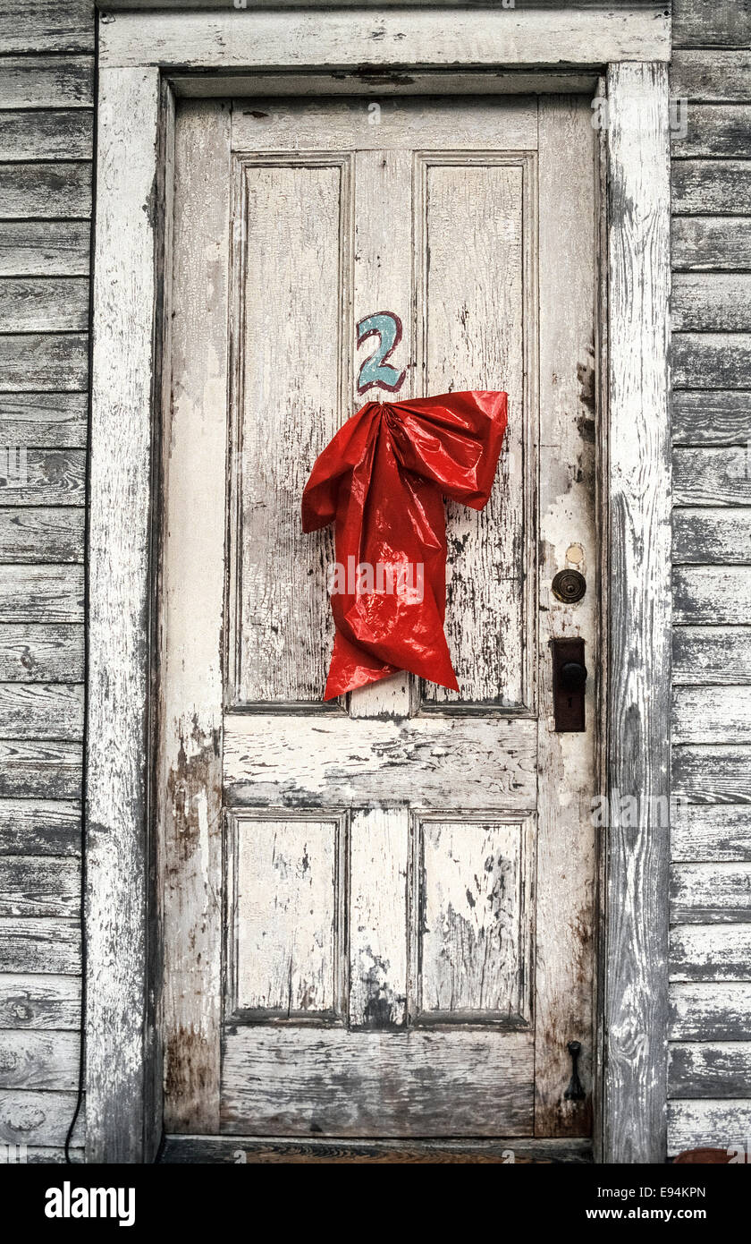 A sagging red plastic Christmas bow makes an unsuccessful attempt to add holiday cheer to a guestroom door in an - Stock Image