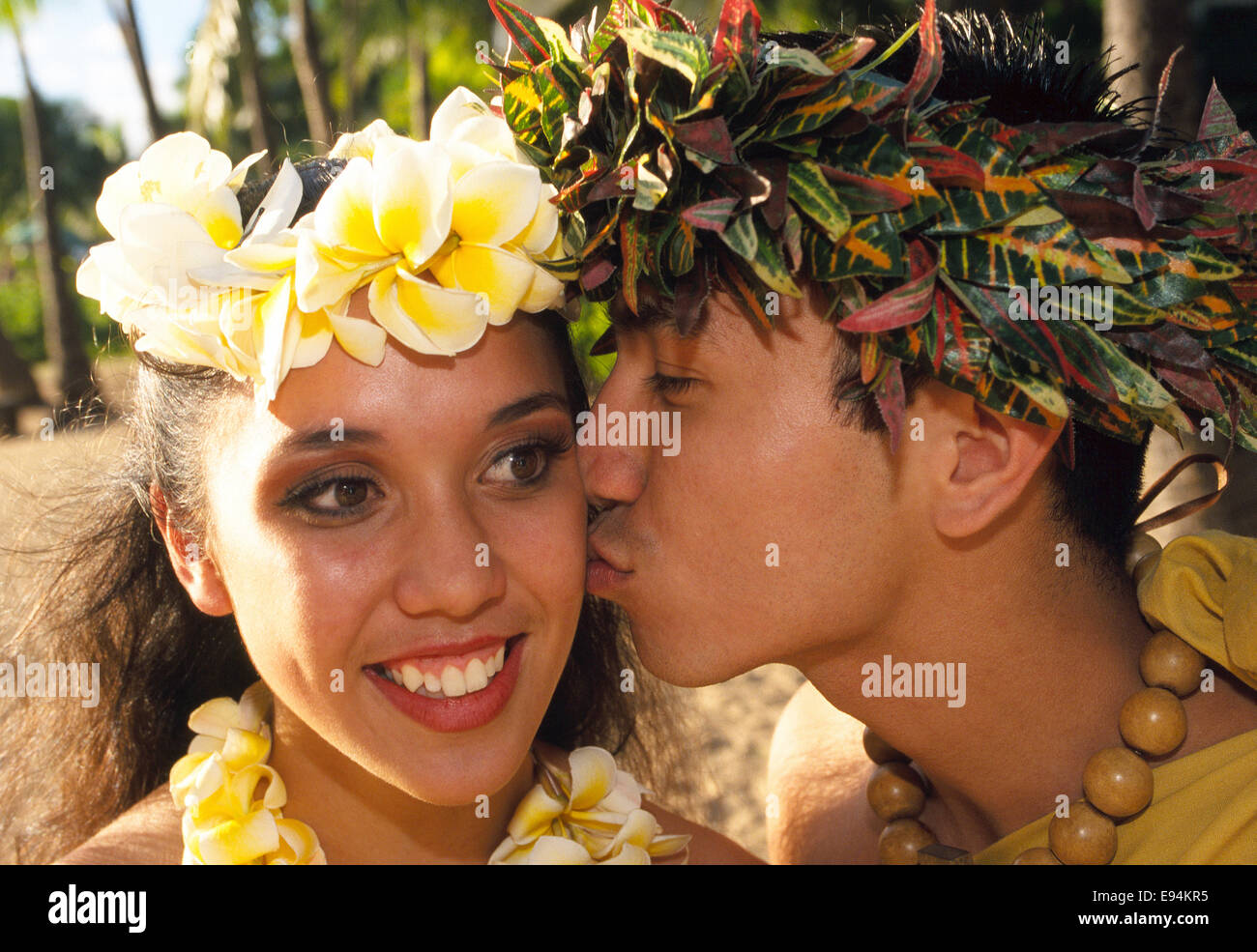 A Hawaiian female hula dancer gets a kiss on the cheek from her fellow entertainer after their performance at a - Stock Image